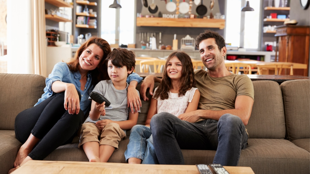 A happy family sitting on the couch.