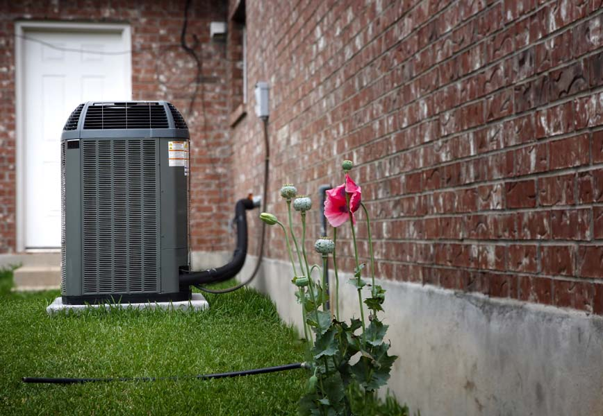 Air conditioner in backyard of home in summer time