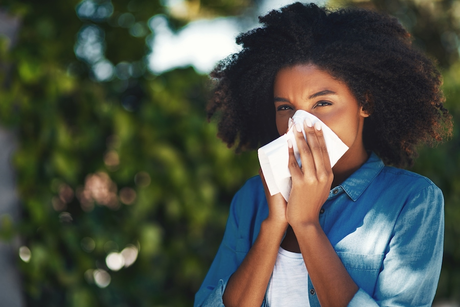 Woman blowing her nose due to not using her ac to help with allergy symptoms