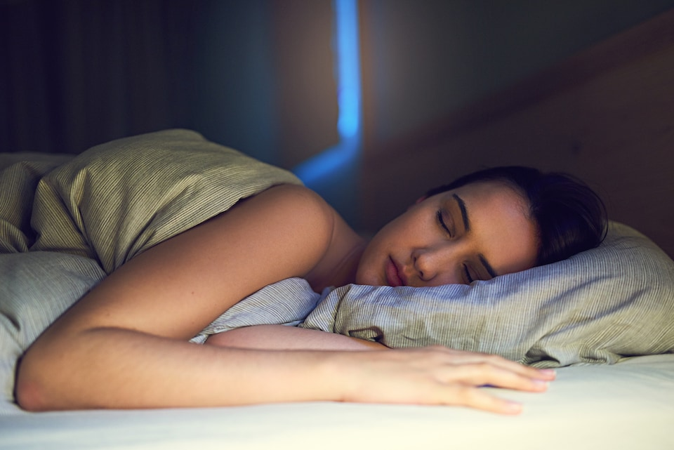 Shot of a young woman sound asleep in her bedroom while sleeping comfortably with air conditioner on