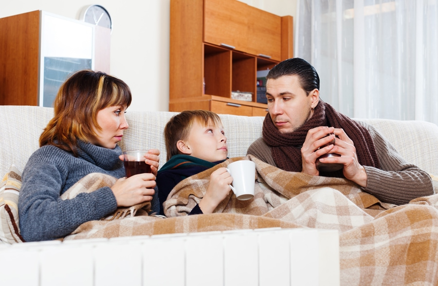 Family snuggled on couch with blanket trying to stay warm and decide if it's time to buy a new furnace.