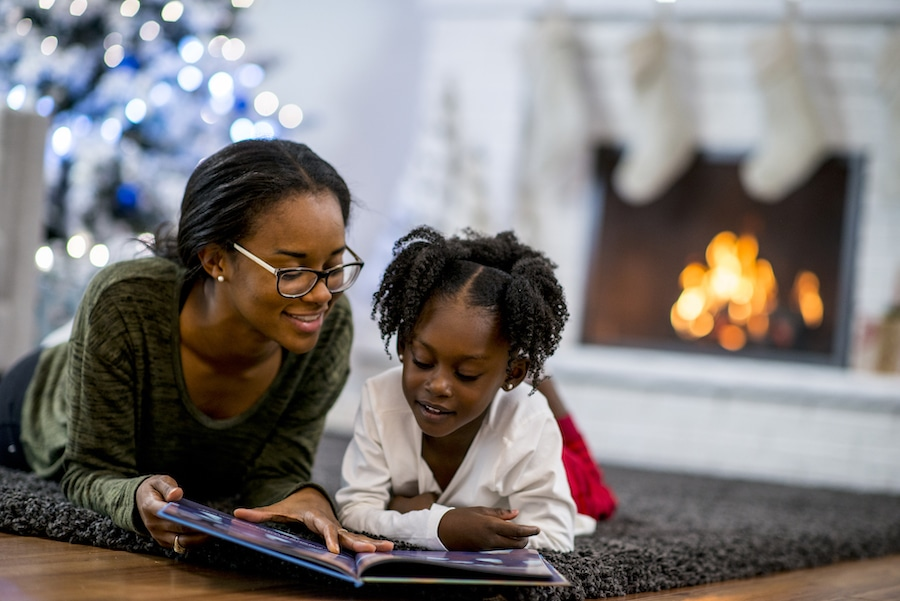 Mom and daughter relaxing by the fire after learning how they can save money on their heating bill this winter.