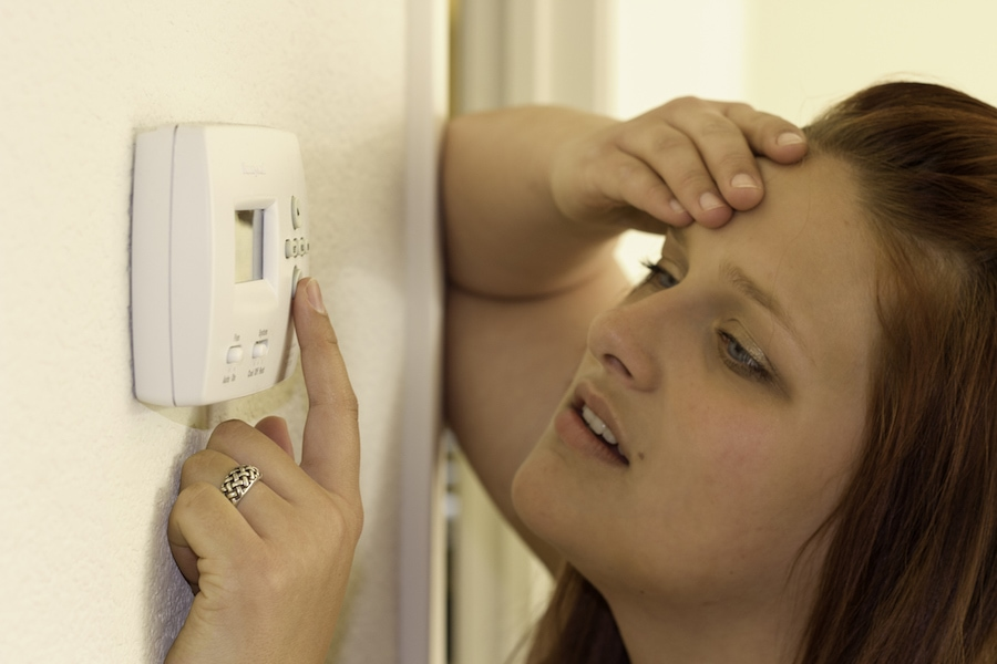 Woman trying to figure out how to troubleshoot her thermostat while following some tips.