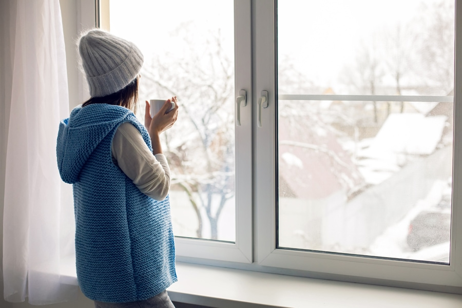 Woman looking out window in winter time trying to figure out how she can make her furnace last longer.
