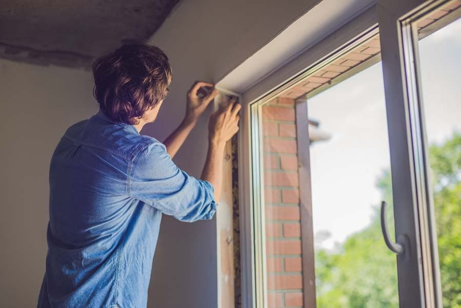 Man checking the window seal as part of the heat gain prevention tips.
